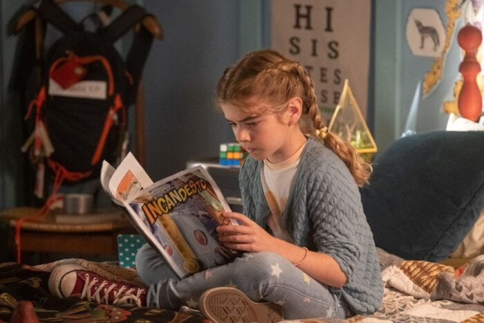 Flora reads her father's comic book on her bed.