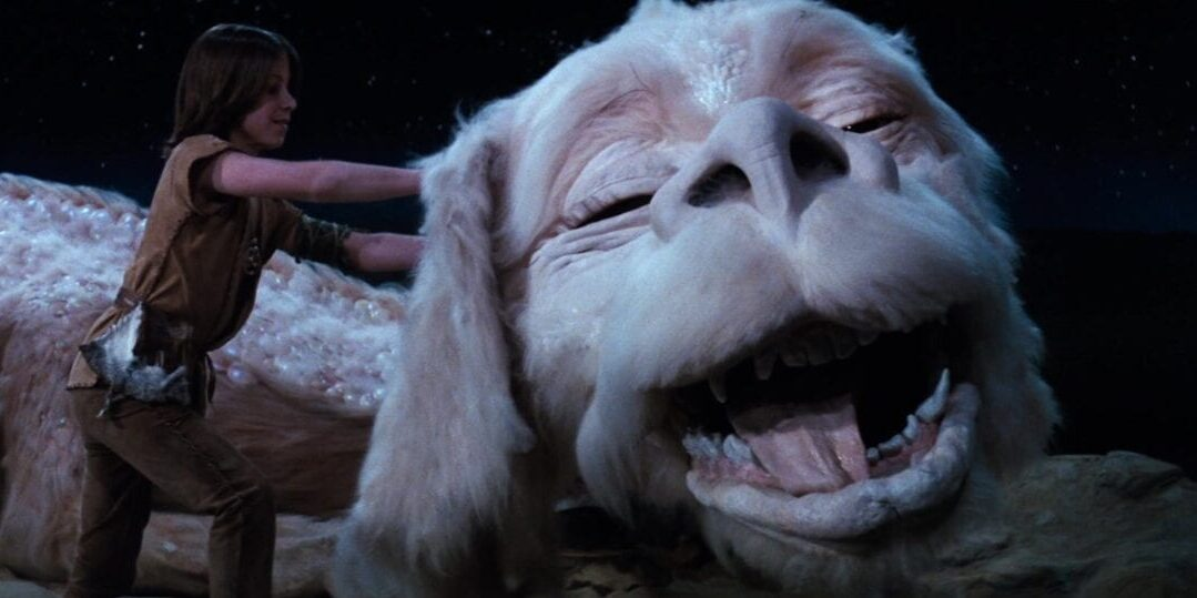 Atreyu scratches Falkor behind the ear, Falkor smiles happily
