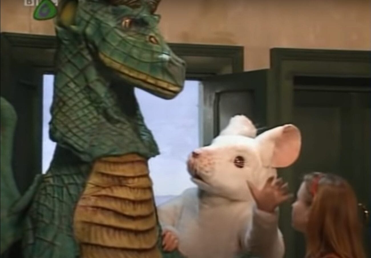 A mouse looks up at a dragon as a girl looks on