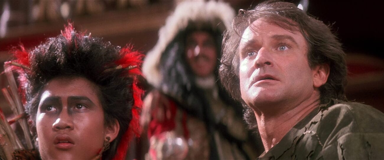 Rufio and Peter look at something, shocked, while Hook stands behind them
