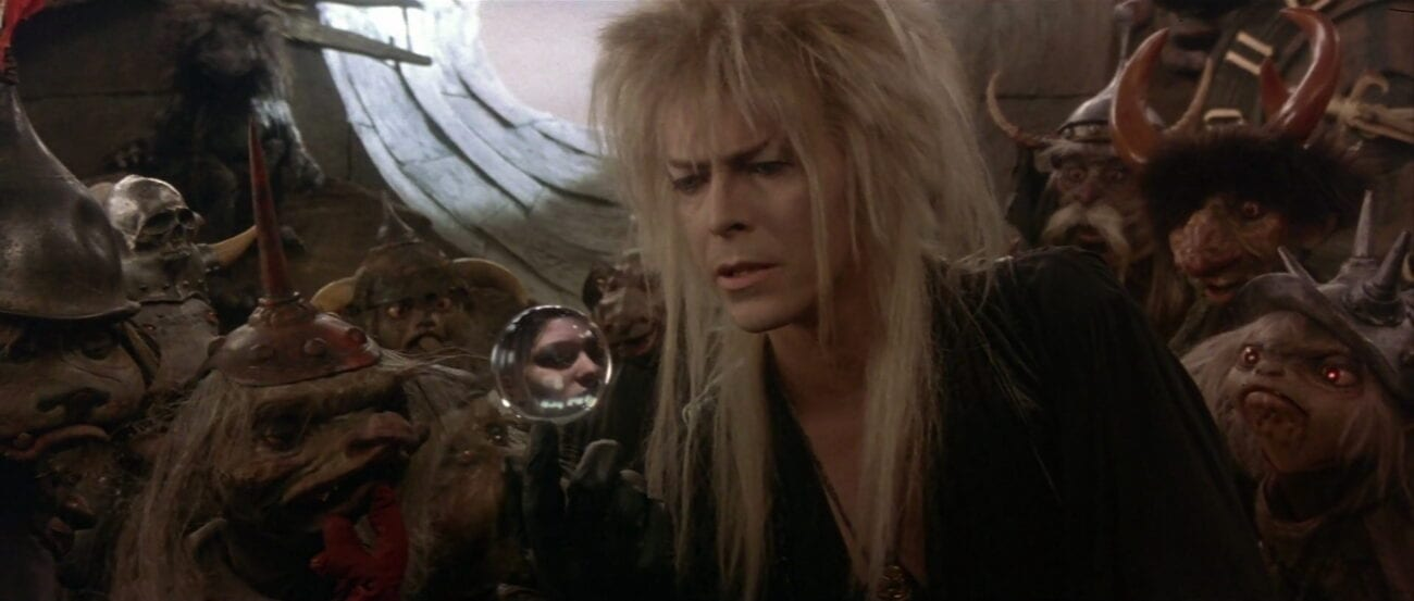 Surrounded by goblins, Jareth looks at Sarah in his crystal ball