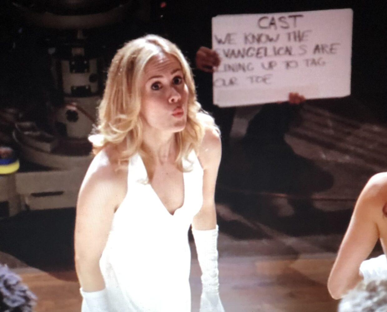 "Harriet, wearing a white formal gown for a sketch, faces up, with a ""WTF?"" look on her face, with a cue card in the background"