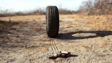 a tire rolls down a dirt road toward an empty beer bottle