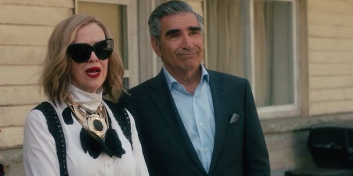 Moira and Johnny standing outside the motel, Moira wearing sunglasses and Johnny a suit in Schitt's Creek