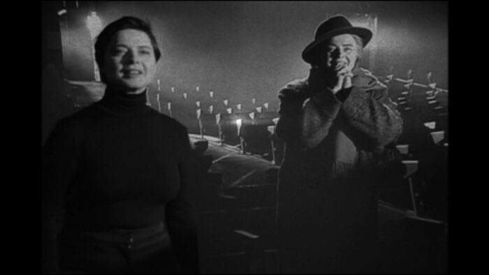 """Still from My Dad is 100 Years Old. Actress Isabella Rossellini portrays herself and director Frederico Fellini (right). Rossellini is wearing a black turtleneck, """"Fellini"""" a hat, coat, and scarf. They both look pleased and excited"""