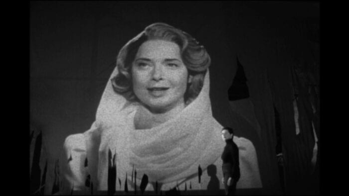 Still from My Dad is 100 Years Old. Isabella Rossellini plays her real-life mother, Ingrid Bergman, as she is projected on a large screen. In front of her is the real Rossellini, looking off to the side.