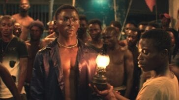 A young man shines an oil lamp up to the puzzled looking Roman as inmates circle behind them