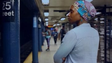 Still from a newly added short film on the Criterion Channel. Actress Chinasa Ogbuagu plays Kamara in On Monday Last Week. She is standing waiting for a subway. She is standing with her arms casually crossed and her back is slightly turned towards the camera.