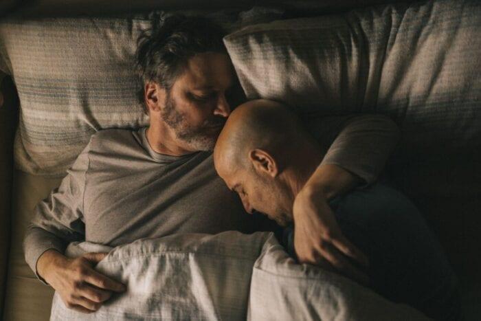 Sam kisses Tusker's head in bed.
