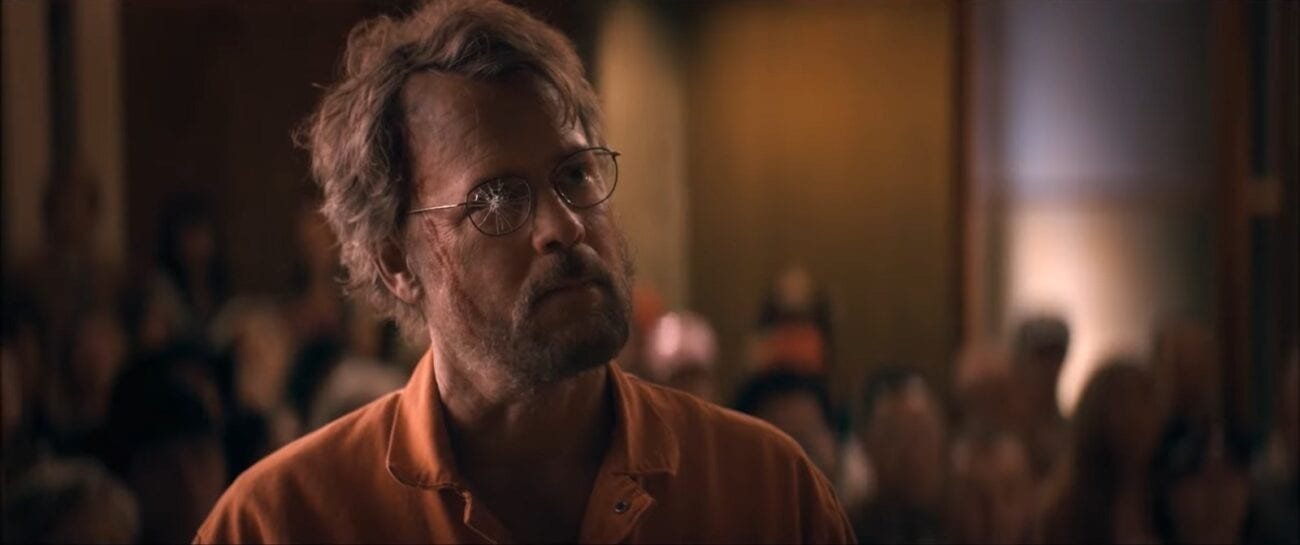Glen stands in a courtroom, clothed in an orange prison jumpsuit, the right lens of his glasses broken in The Stand Episode 8