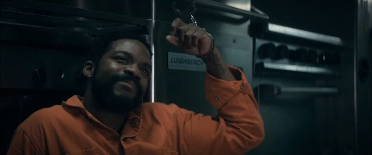 The Stand S1E8 - Larry sitting on the ground in an orange jumpsuit, handcuffed to a piece of kitchen equipement, smiling up at someone