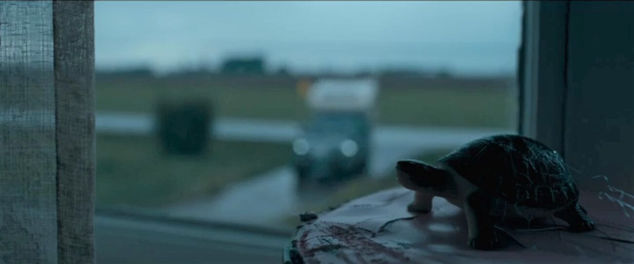 The Stand S1E9 - A turtle figurine looks out through a window at a truck with a camper pulling into a driveway