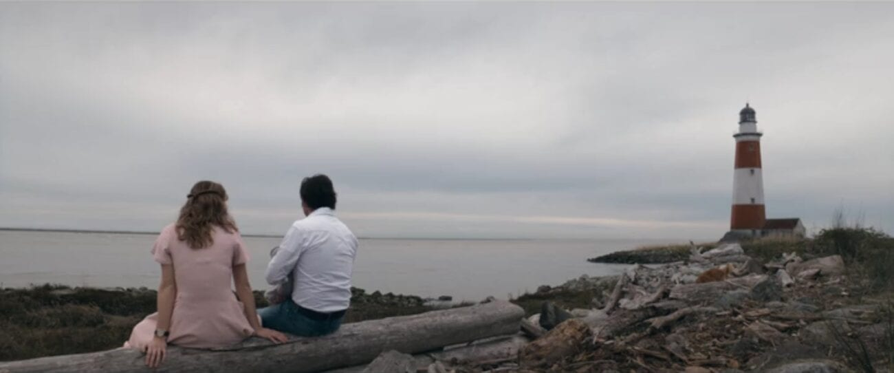 The Stand S1E9 - Frannie and Stu sit on a rocky Maine beach, looking out over the ocean, with a lighthouse nearby