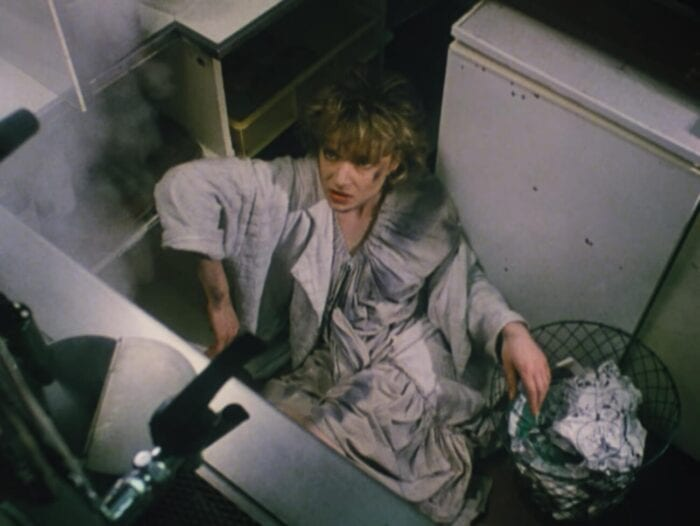 Fro above, woman cowers in a corner near a trash can filled with crumpled paper. She looks warily to some dissipating fog.