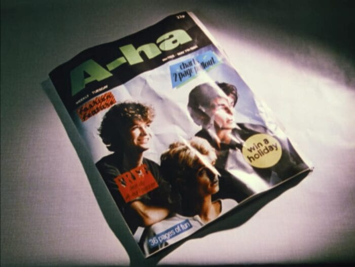A magazine on an angle. It's title is A-ha, and the three band members' faces are on the cover.