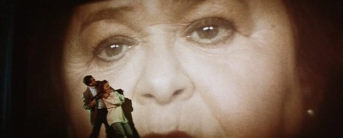 a man holds a woman hostage standing in front of a movie screen displaying a zoomed in view of an older woman's face