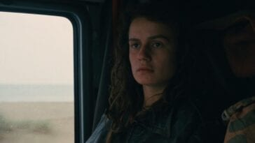 Mona sitting as a passenger in a car in Vagabond.