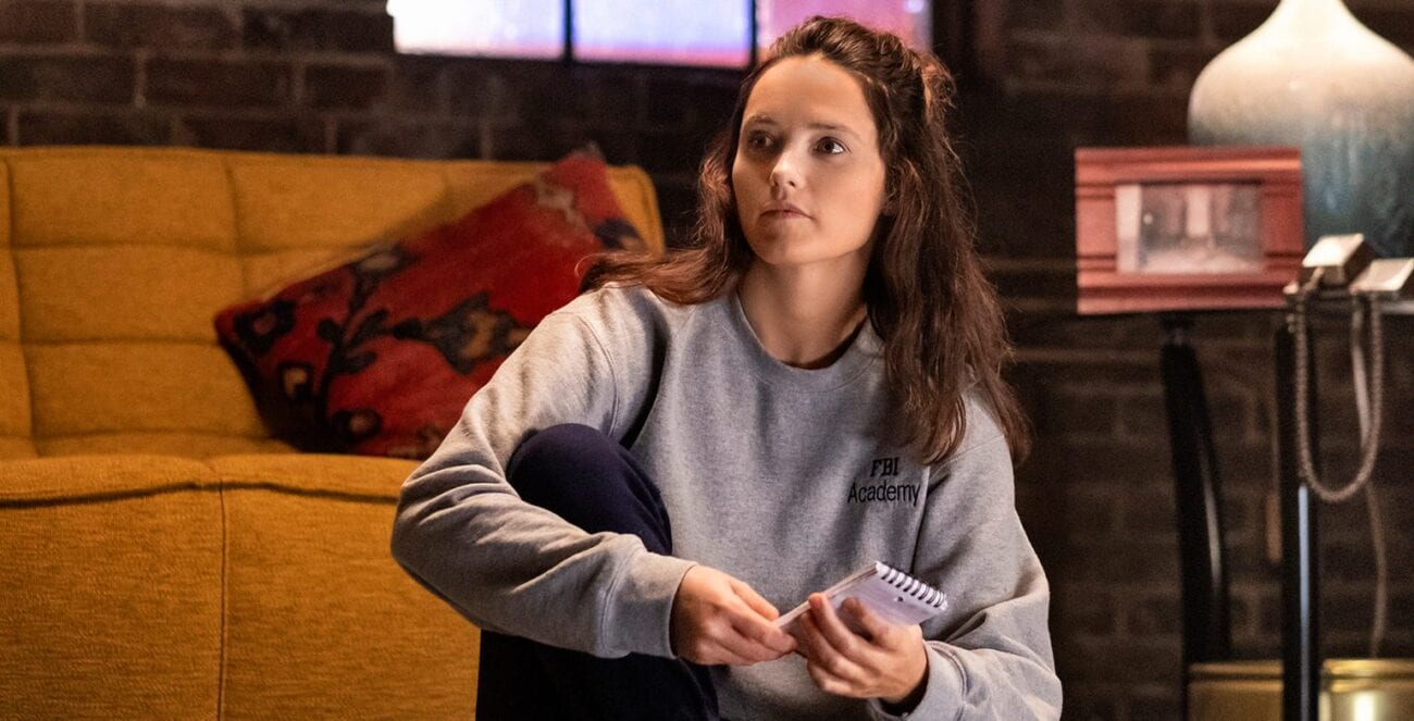 Clarice sits on the living room floor, wearing sweats and a sweatshirt, holding a notepad