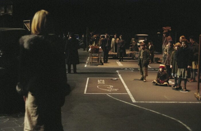 a woman walks on a empty stage, the ground marked with chalk. there are being sitting in the distance