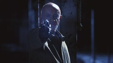 Mike Ehrmantraut aims a revolver off screen in dim lighting