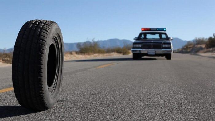 a tire rolls down a desert road followed by a police cruiser