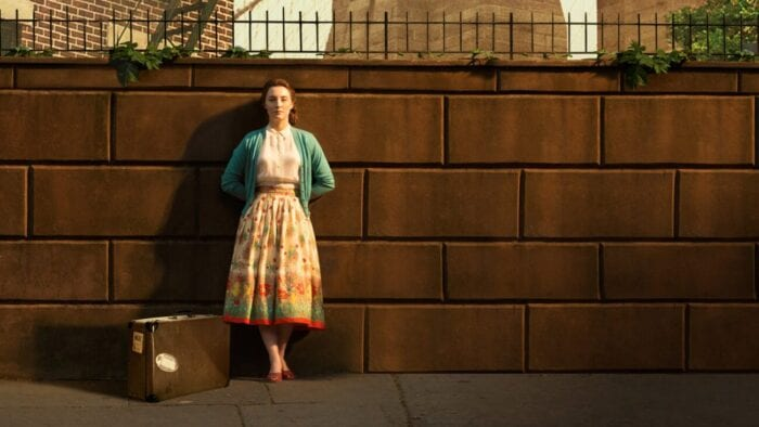 Eilis stands on a sidewalk wall next to a suitcase