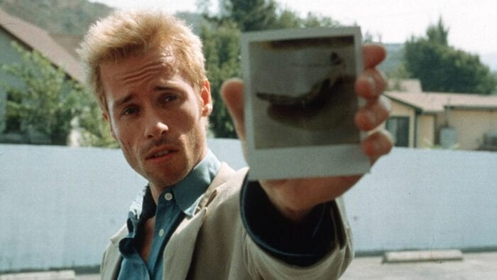 Leonard (Guy Pearce) shows the polaroid.