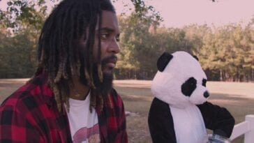 Kamus and the panda bear stand outside looking off camera to the right