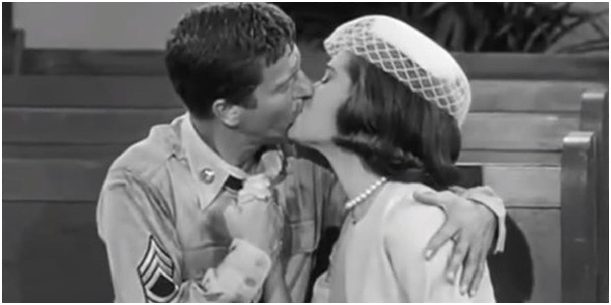 Rob and Laura on their wedding day, sitting in a pew and kissing in The Dick Van Dyke Show