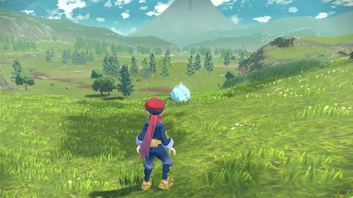 a pokemon trainer stands in a huge field, overlooking a rhydon