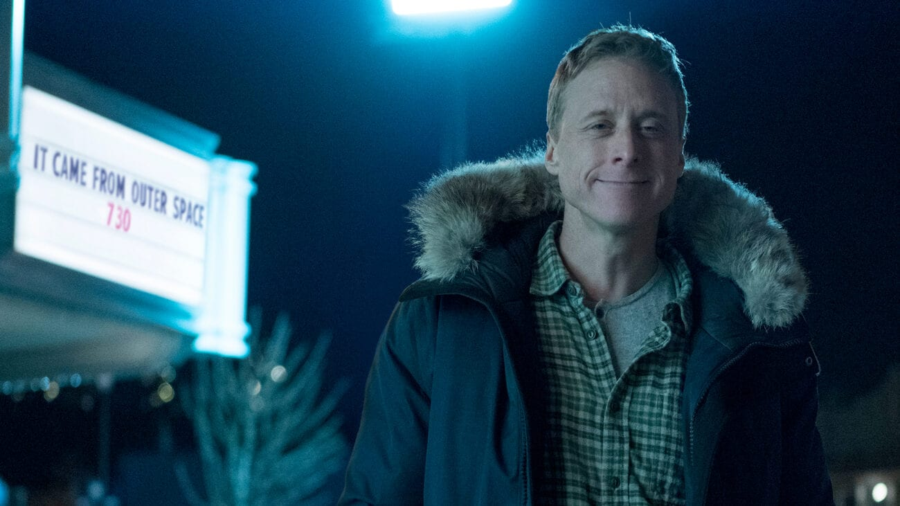"Alan Tudyk smirks with a sign reading ""it came from outer space"" behind him in Resident Alien"
