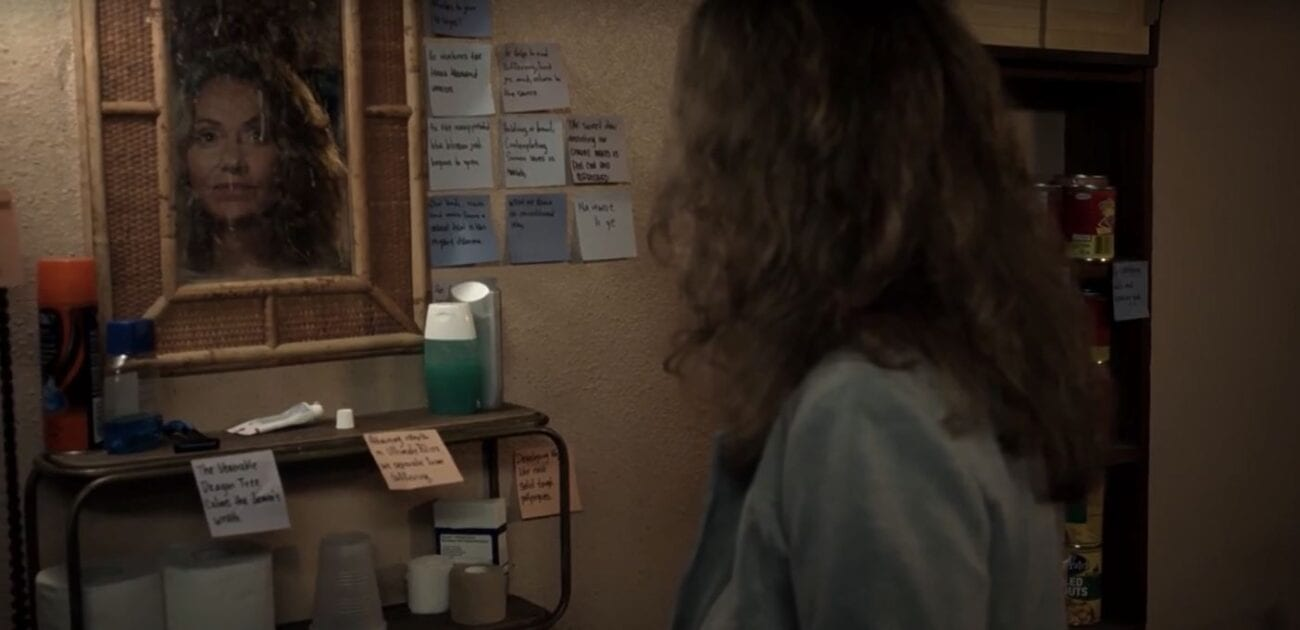 Mary looks into a mirror surrounded by post it notes with koans and such on them in John's apartment