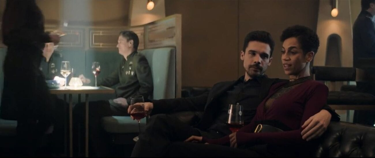 Holden sits on a couch with his arm around Naomi as they hold glasses of wine at a party in The Expanse Season 5 Finale, Nemesis Games