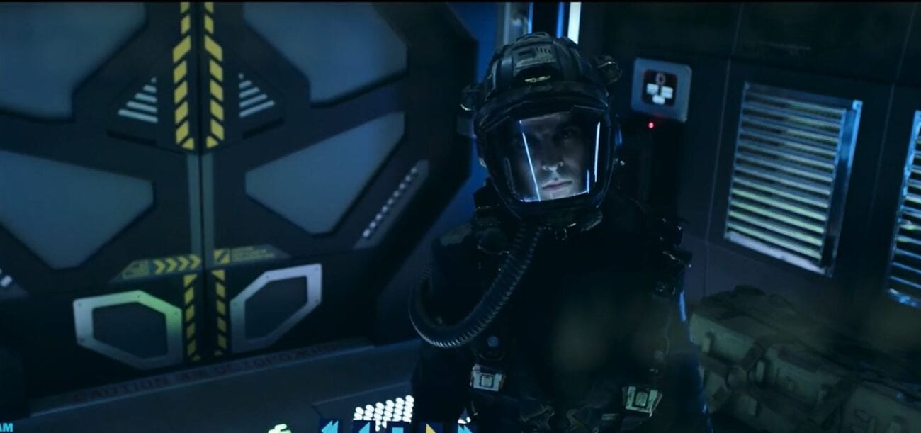 Marco looks up at a camera as he wears a spacesuit in an airlock in the finale of The Expanse Season 5