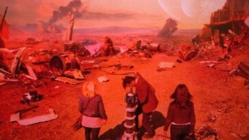 Jo, 11, and Sarah Jane stand around a mechanical device on a red-tinted alien planet