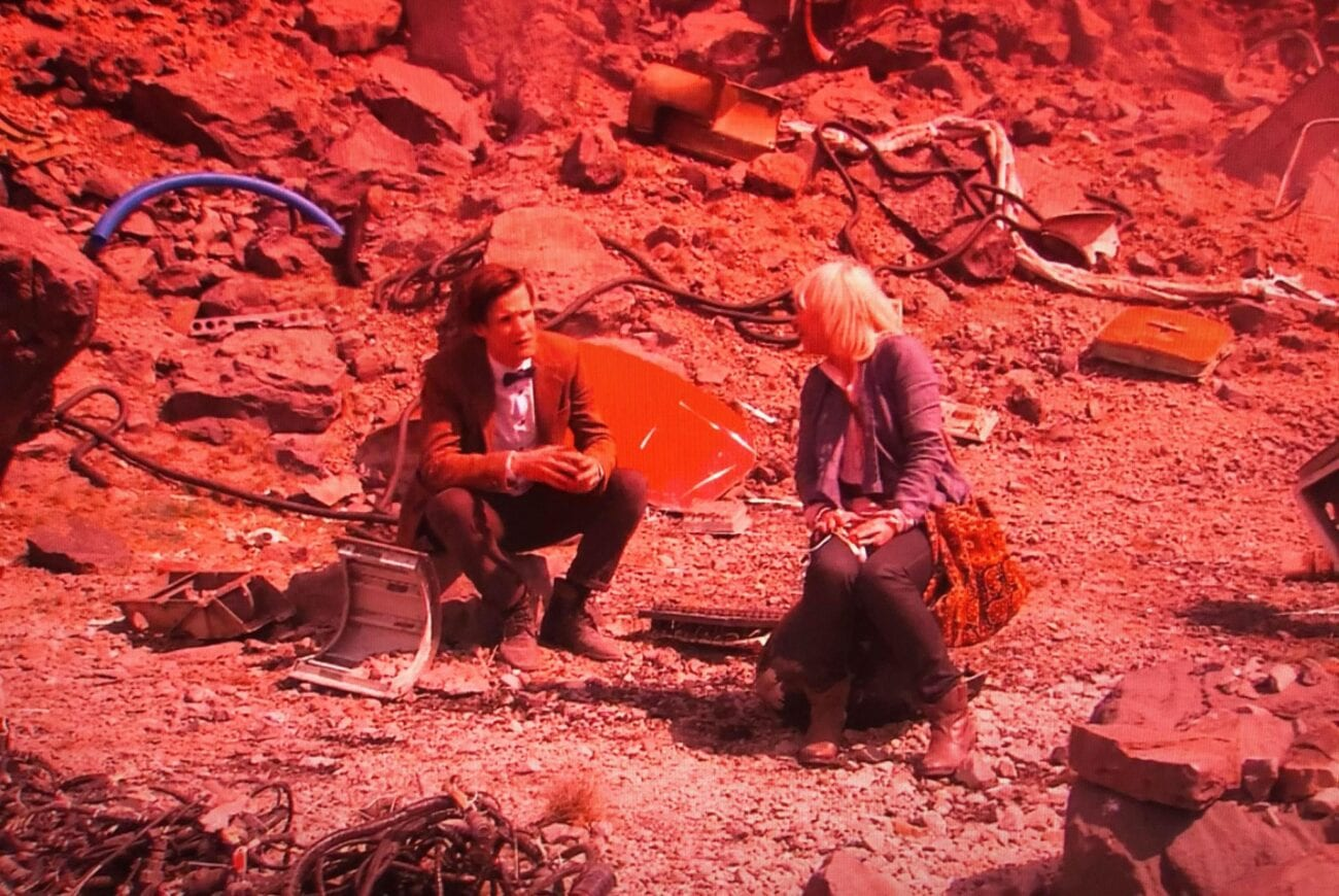The 11th Doctor and Jo Grant sit in a quarry, on a red-tinted planet, talking