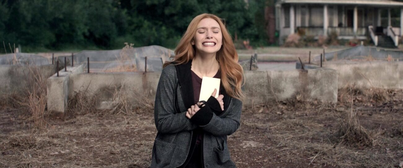 Standing in the middle of a lot for an unbuilt house, sobbing Wanda holds documents close to her chest.