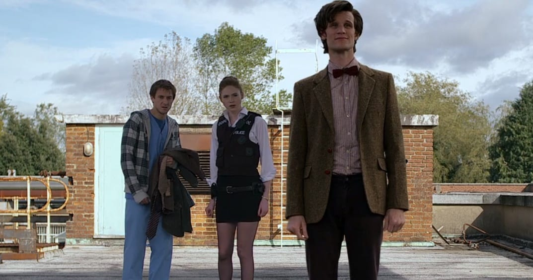 Rory (Arhur Darvill), Amy (Karen Gillan) and the Doctor (Matt Smith) jn his new costume standing on a roof looking toward the camera