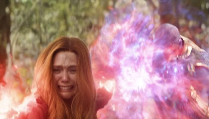 Wanda holding back Thanos from behind while she is visibly distressed destroying the infinity gem in Vision.