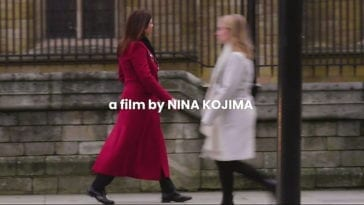 "Two people walk towards each other on a sidewalk in a somewhat blurry still as ""a film by Nina Kojima"" appears on screen"