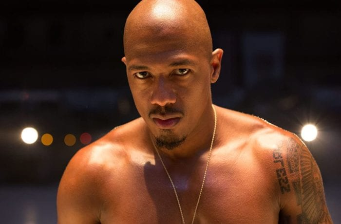 Rapper Chi-Raq performs shirtless under a spotlight on stage.