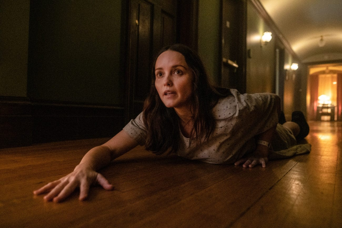 Clarice, in a hospital gown, crawls along a polished wooden floor on her belly