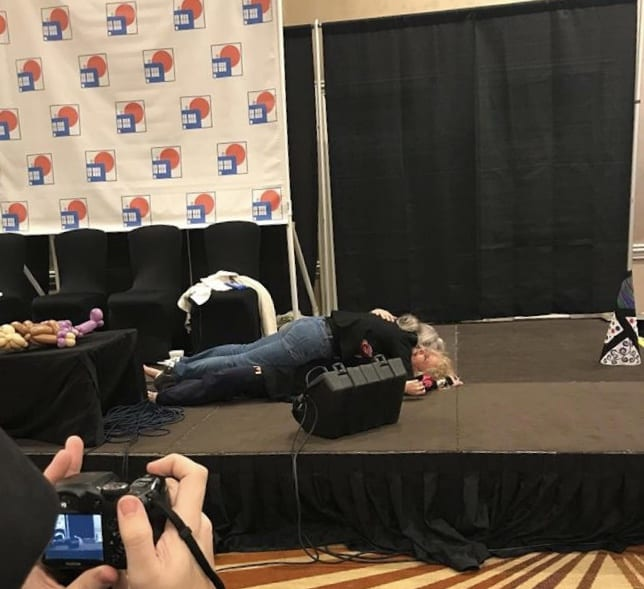 A convention stage where a woman lies flopped on top of another, in an entirely ridiculous and un-erotic way