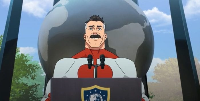 Omni-man delivers his eulogy for the Guardians of the Globe. He is standing at a podium with a globe statue behind him.