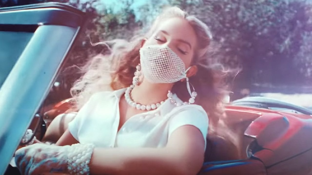 Lana driving a car with a mesh, beaded mask on.