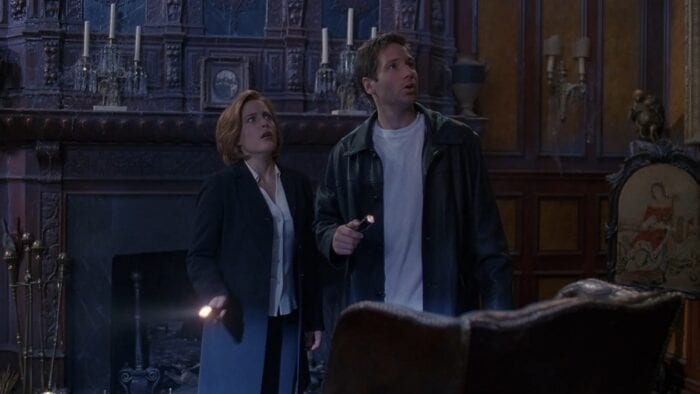 Scully and Mulder are spooked as they stand in front of the mantel in a haunted house