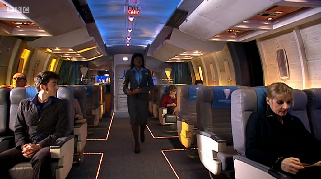 The hostess walks down the centre aisle of the train car in Doctor Who Midnight