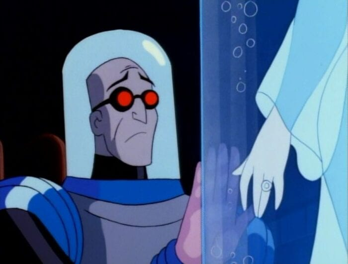 Mr Freeze, in his containment suit, looks longingly into the glass in front of him, where we see the arm of his frozen wife Nora.