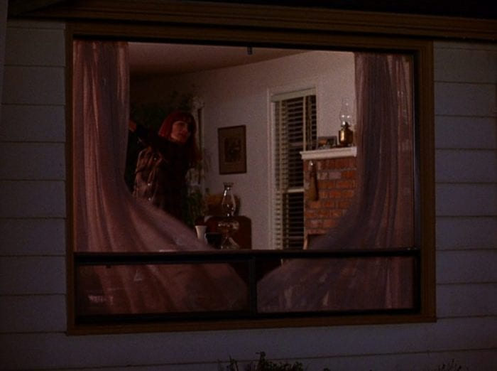 Nadine Hurley opening drapes in her house and peering outside