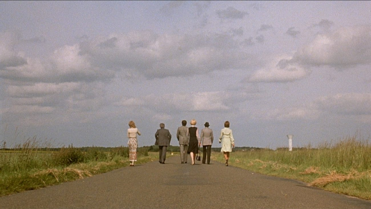 A long-shot behind the backs of the main characters as they walk along a road in the countryside